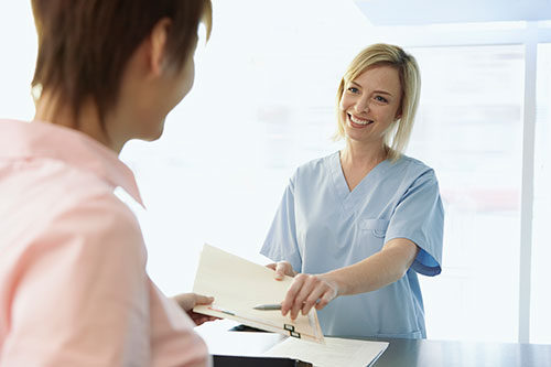 Medical assistant handing patient forms